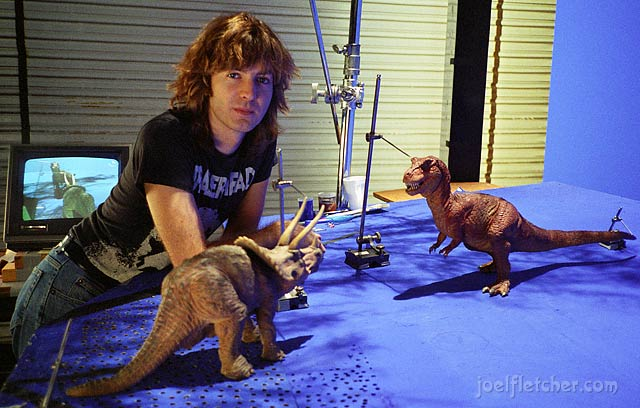 Animator Kent Burton with two dinosaur puppets.