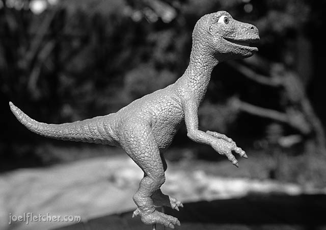 A baby tyrannosaurus sculpted in clay. edge