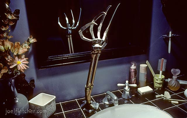 Scary claw pops out of a bathroom sink. edge