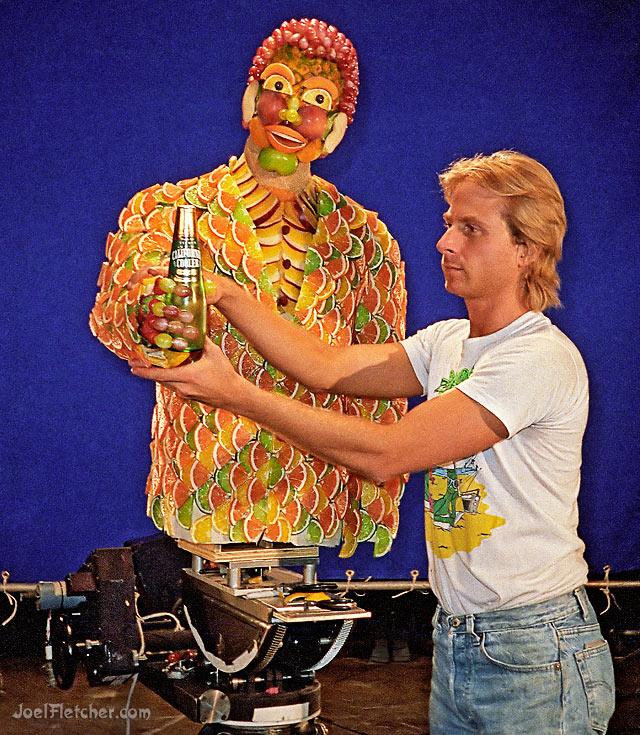 Animator poses life size puppet made of fruit. edge