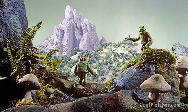 Frog and Toad view a distant mountain. edge