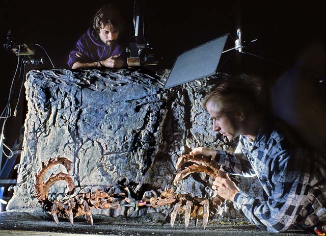 Cameraman and stop-motion animator filming giant alien scorpions. edge