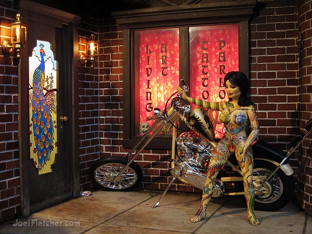 The Living Art Tattoo Parlor with Harley Davidson motorcycle and inked woman. edge