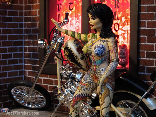 Miniature sculpture of a woman with hand painted tattoos. edge