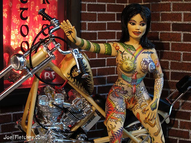 Scale model of girl tattooed with alchemy images. edge
