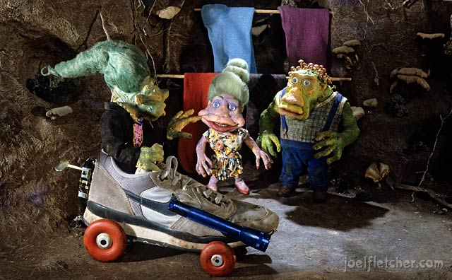 Troll family in underground home greets their son arriving in a car made from a shoe. edge