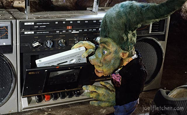 Teenage troll inserting cassette into stereo. edge