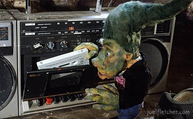 Teenage troll inserting cassette into stereo. edge