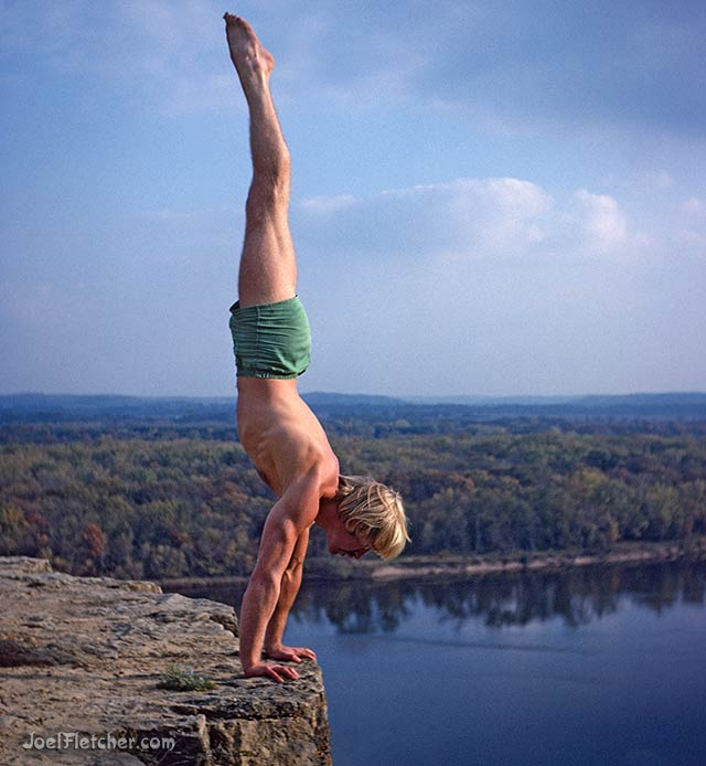 Man performs a handstand on a cliff above a river