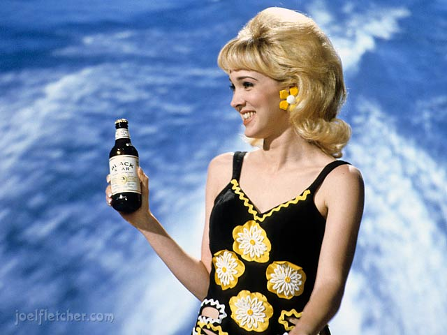 1960's water skiing girl with bouffant hair holds beer. edge