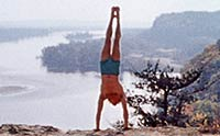 Handstanding figure over river valley