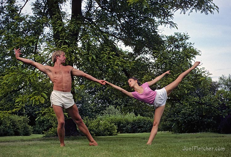Two dancers perform a classic pose in a garden. gallery