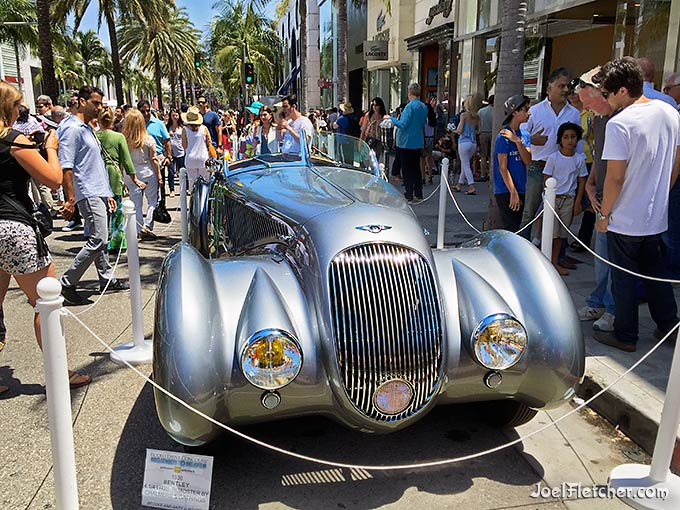 Crowds surround a vintage Bentley automobile.