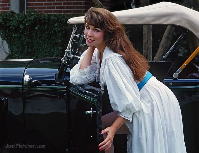 Beautiful woman in white dress with vintage automobile