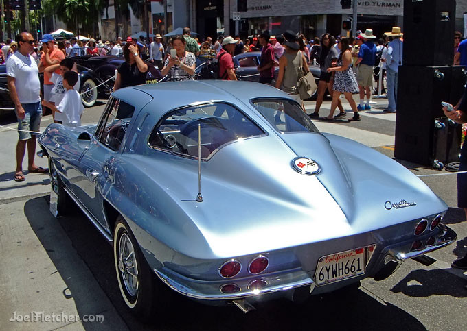 A rear view of a silver 1963 Corvette at a car show.