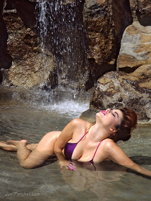 Beautiful woman relaxes in a pool with waterfall.