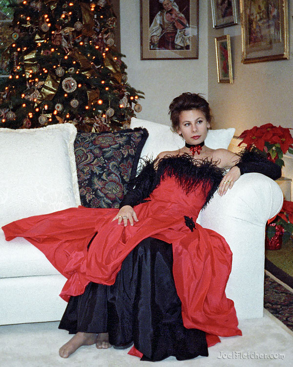 Beautiful woman wearing a red dress in a Christmas decorated home.