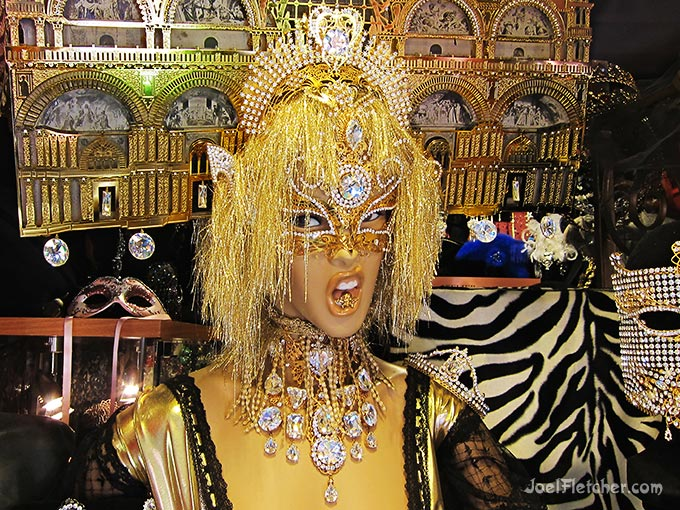 Mannequin covered with bling in store window.