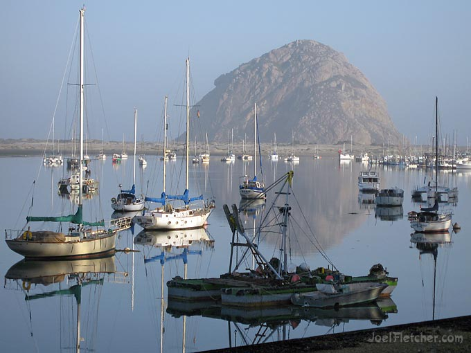Boats in a harbor with giant rock in the background.