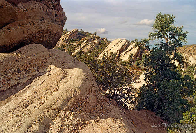 Conglomerate boulders in front of a dramatic landscape.