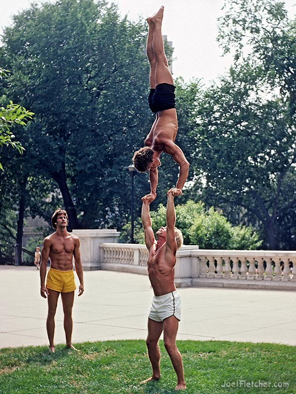 An acrobat holds a handstanding man high up in the air