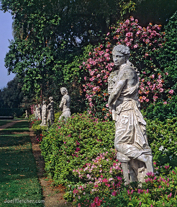 Rows of statues surrounded by flowers and trees