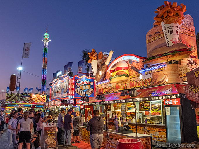 People wait in line at colorful fair food booths at dusk