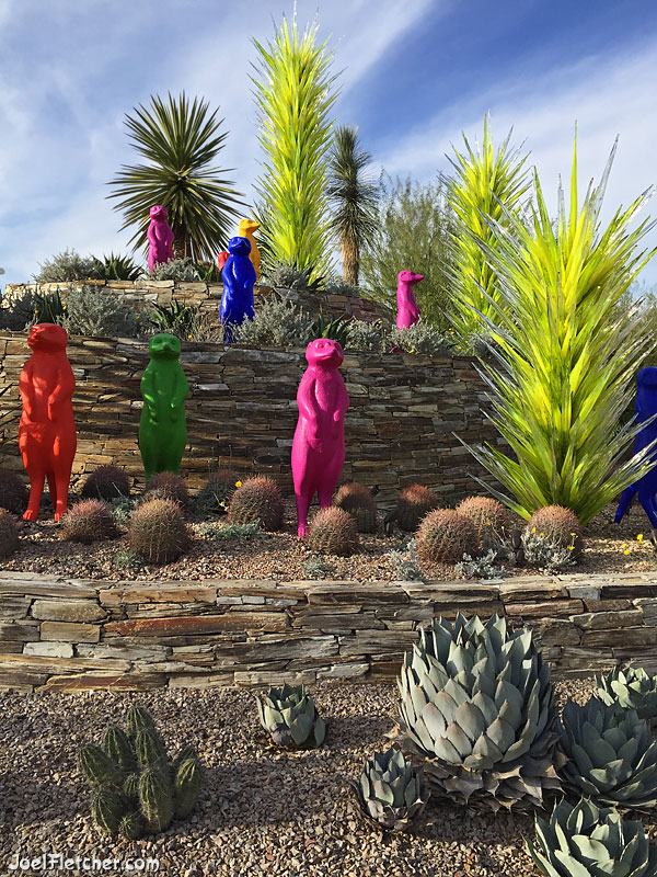 Vibrant multicolored plastic and glass sculptures in a desert landscape.